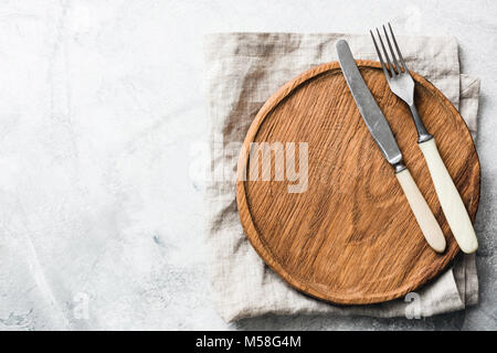 Vintage silverware and wooden board on grey concrete background. Top view, copy space for text - Stock Photo