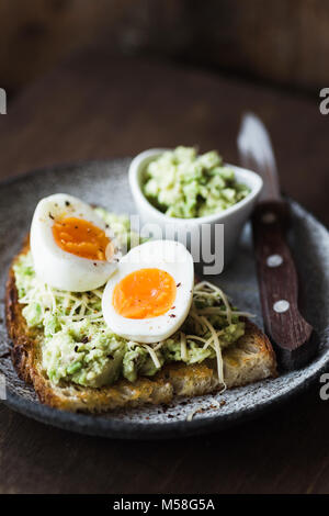 Mashed avocado, egg and cheese on toasted bread. Healthy lifestyle, healthy eating concept. Dark food photo, selective - Stock Photo