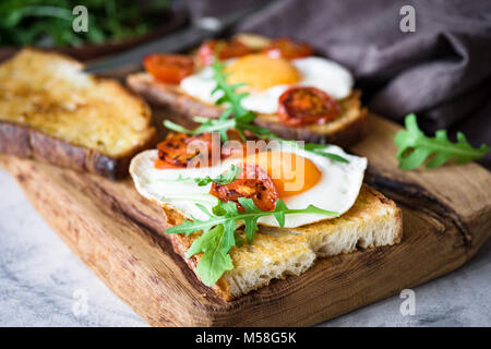 Healthy breakfast toast with egg, roasted tomato and arugula on rustic wooden cutting board. Closeup view - Stock Photo