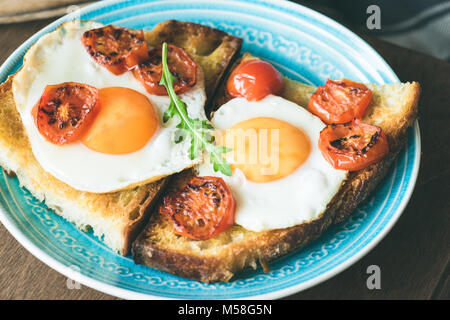 Breakfast toast with egg, roasted tomatoes and arugula salad on blue plate. Closeup view - Stock Photo
