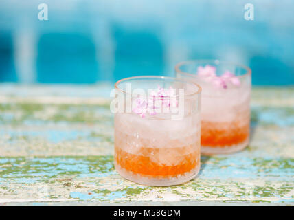 Lilac lemonade water with flowers by the pool - Stock Photo