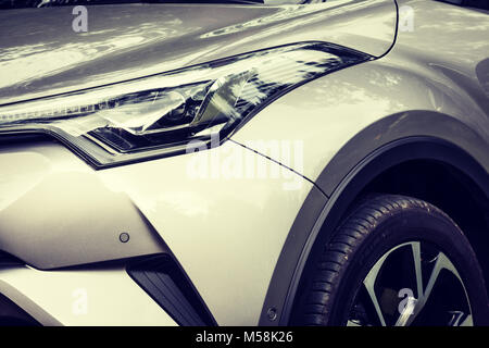 Concept shot of headlamp and part of modern crossover car - Toyota CH-R. - Stock Photo