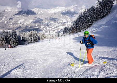 Male skier in French Alps in winter snow skiing on red route ski slope Grand Cret to Vercland, Samoens, Haute Savoie, - Stock Photo