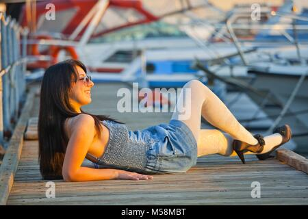 Young woman legs heels lying accros peer and smiling away wearing White tights pantyhose beauty - Stock Photo