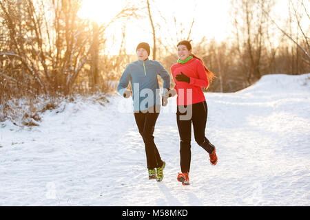 Photo of two athletes on morning run in winter park - Stock Photo