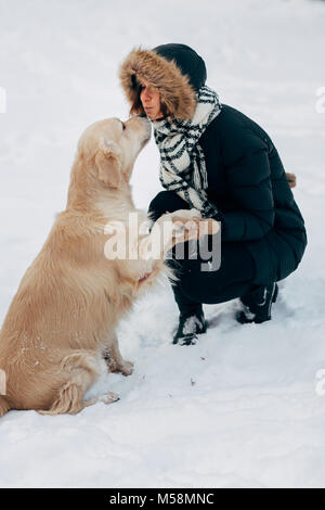 Picture of labrador giving paw to girl in black jacket on winter day - Stock Photo
