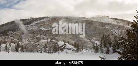 Panoramic landscape of snow covered field against Roaring Mountain with active geyser steam vents with pine trees - Stock Photo
