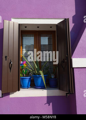 Open window shutters on purple home in Burano Italy - Stock Photo