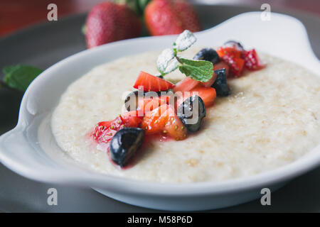 Bowl of oatmeal porridge with fruits and greens, hot and healthy food for Breakfast, macro - Stock Photo