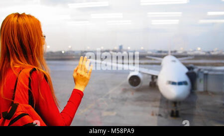 Young attractive woman with red hair and glasses looking at airplanes on runway airport - Stock Photo