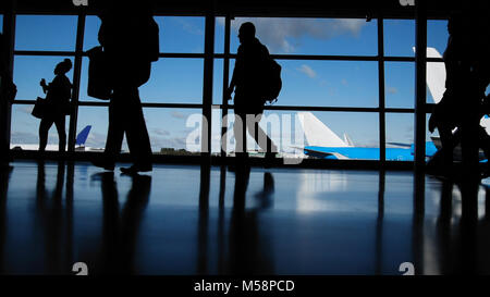 Travellers with suitcases and baggage in airport walking to departures in front of window, silhouette - Stock Photo
