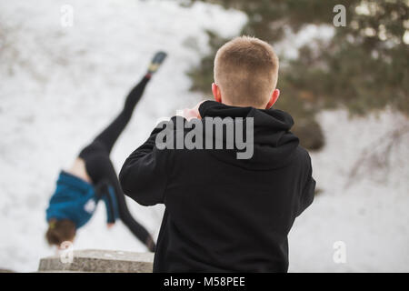 Teenager boy looking to acrobatic jump girl in winter city park - parkour concept - Stock Photo