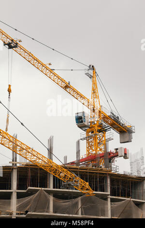 Crane and building under construction on cloudy sky - Stock Photo