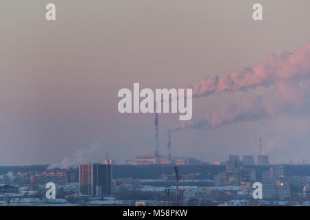 Industrial landscape with smoking pipes at winter sunset, global warming concept - Stock Photo