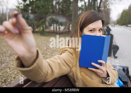 A young woman holds glasses in hand and book - sitting on the bench at park - Stock Photo