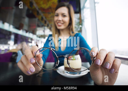 Pretty young girl holding glasses in hands sitting in cafe, ophthalmology - Stock Photo