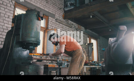 Man blacksmith forges the metal at the mechanical hammer - small business - Stock Photo