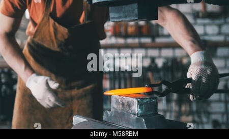 Automatic mechanical hammering - blacksmith forging red hot iron on anvil, telephoto - Stock Photo