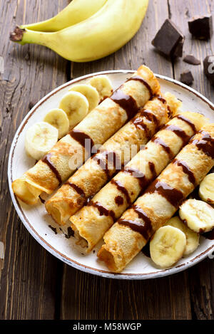 Tasty crepe roll with banana slices on wooden table. Thin pancakes, crepes with chocolate sauce. Top view - Stock Photo