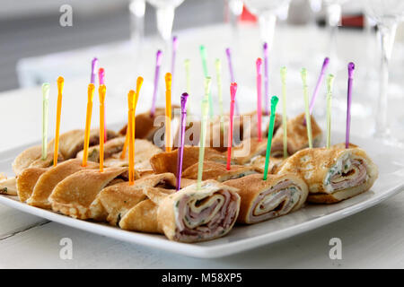 Snack for a buffet table rolls of pancakes and meat - Stock Photo