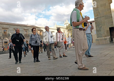 A tour group in in Oaxaca, Mexico walks by a cathedral in the heart of the historic area of town. - Stock Photo