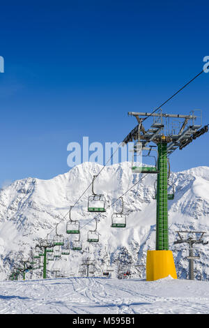 Chairlift at snow covered Italian ski area in the Alps - winter sports concept with copy space - Stock Photo