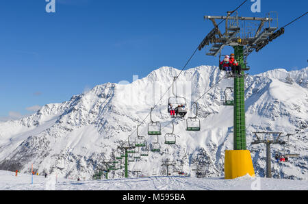 La Thuile, Italy - Feb 18, 2018: Chairlift at snow covered Italian ski area in the Alps - winter sports concept - Stock Photo