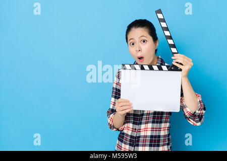 beautiful young woman playing clapboard standing in blue background and looking at camera making surprised emoticon face.