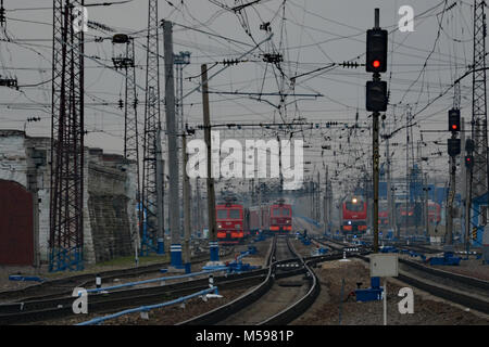 Three typical Russian trains amid a mass of wires and gantries on the Trans Siberian Railway - Stock Photo