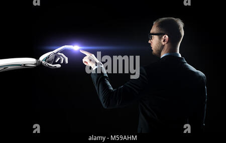 robot and human hand flash light over black - Stock Photo