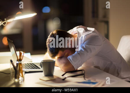 tired businessman lying on table at night office - Stock Photo