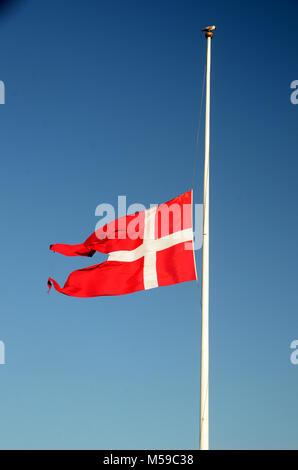 The danish flag Dannebrog on half mast - Stock Photo