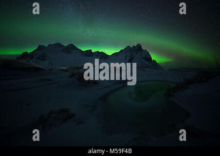 Green eye, aurora borealis at Stokksnes in Iceland - Stock Photo