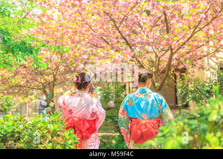 Asian women in traditional kimono take photo of cherry blossom trees along Philosopher's walk during Sakura, sping - Stock Photo