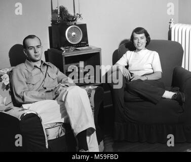 Young couple enjoy time in their living room with their radio and turntable sound system, ca. 1950. - Stock Photo