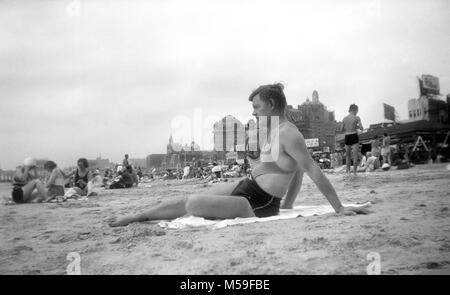 A man wears a stylish bathing suit with a man bra feature lounges in the sand in Atlantic City, New Jersey in 1939. - Stock Photo