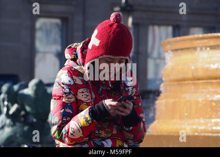 A young Eastern woman using her smartphone in the street on a cold bright winter's day wearing warm winter clothing, - Stock Photo