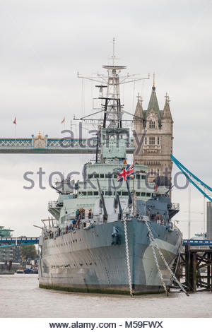 HMS Belfast Second World War Royal Navy warship at anchor in the River Thames with the Tower Bridge in the background, - Stock Photo