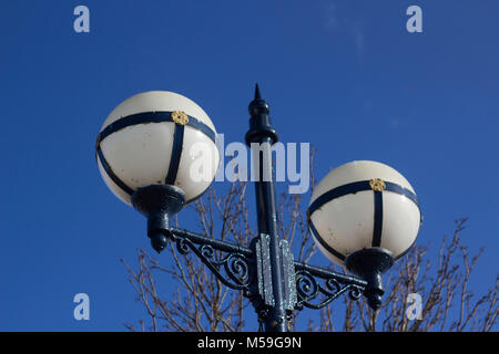 Ornate  retro style decorative vintage style street lamp with white glass globes - Stock Photo