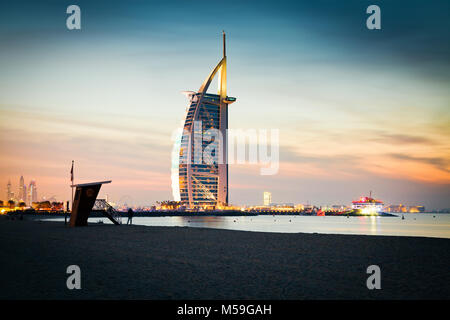 DUBAI, UAE - FEBRUARY 2018 :The world's first seven stars luxury hotel Burj Al Arab at night seen from Jumeirah - Stock Photo
