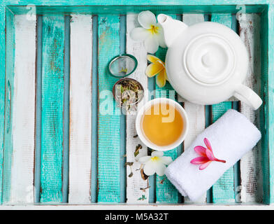 Green tea in white cup and teapot, welcome spa set. Wooden colorful tray. Top view. Copy space - Stock Photo