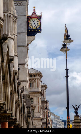 Royal Courts of Justice Clock, at The Strand, London. Row of buildings on left, lamp post on right. Iron statue - Stock Photo