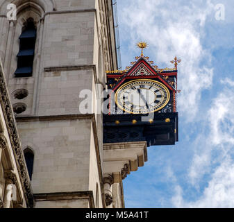 Royal Courts of Justice Clock,  mounted on the outside of the building at The Strand, London.  Angle. Blue sky with - Stock Photo