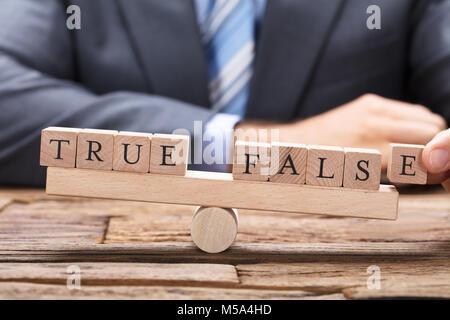 Midsection of businessman with true and false wooden blocks on seesaw at table - Stock Photo