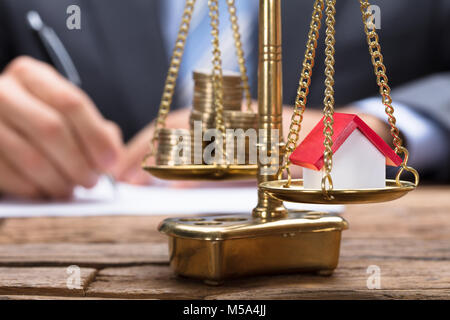 Closeup of model home and coins on golden weighing scale with businessman in background - Stock Photo