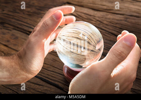 Businessman fortune telling and predicting future at wooden table - Stock Photo