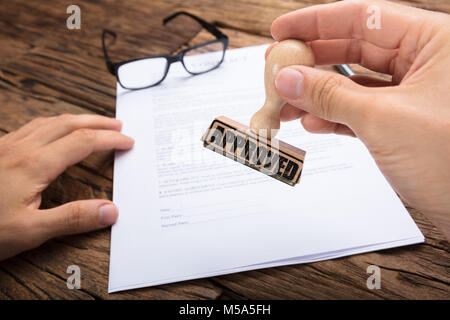 Cropped hands of businessman holding approved stamp over contract paper at wooden table - Stock Photo