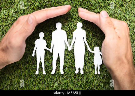 Directly above shot of businessman's hands covering paper family on grass - Stock Photo