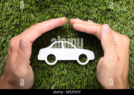 Directly above shot of businessman's hands covering paper car on grass - Stock Photo