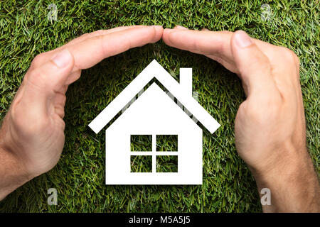 Directly above shot of businessman's hands covering paper house on grass - Stock Photo